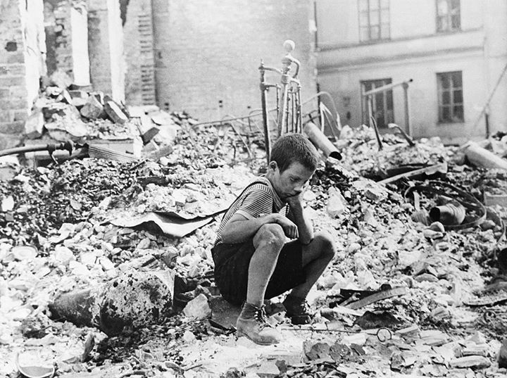 War and despair.  In the wake of the German invasion of Poland a young boy whose home has been wrecked by a bomb sits on the ruins. His facial expression tells a story without words. (Photo by Julien Bryan via Wikipedia).