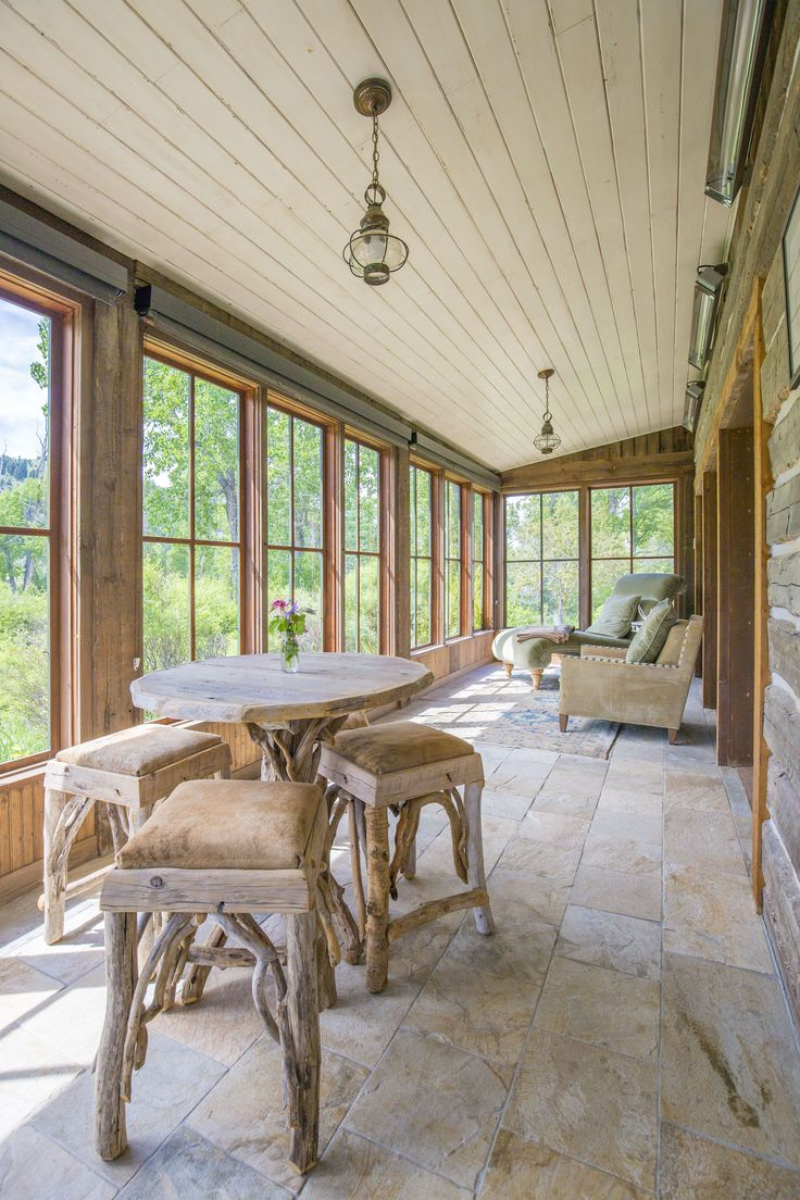 The screened-in porch in Bluebird Cabin at The Ranch at Rock Creek in Southwest Montana. Most of the furniture inside this luxury log home is custom-made. The chaise lounge in the back is ideal for watching raptors fish on our namesake stream.