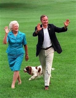 This Aug. 24, 1992 file photo shows President Bush, right, and first lady Barbara Bush walking with their dog Millie across the South Lawn as they return to the White House. (AP Photo/Scott Applewhite)