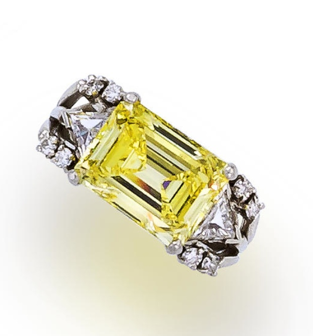 A fancy colored diamond and diamond ring  set with a cut-cornered rectangular step-cut fancy intense yellow diamond, weighing 5.22 carats, flanked by triangular and round brilliant-cut diamonds; mounted in platinum