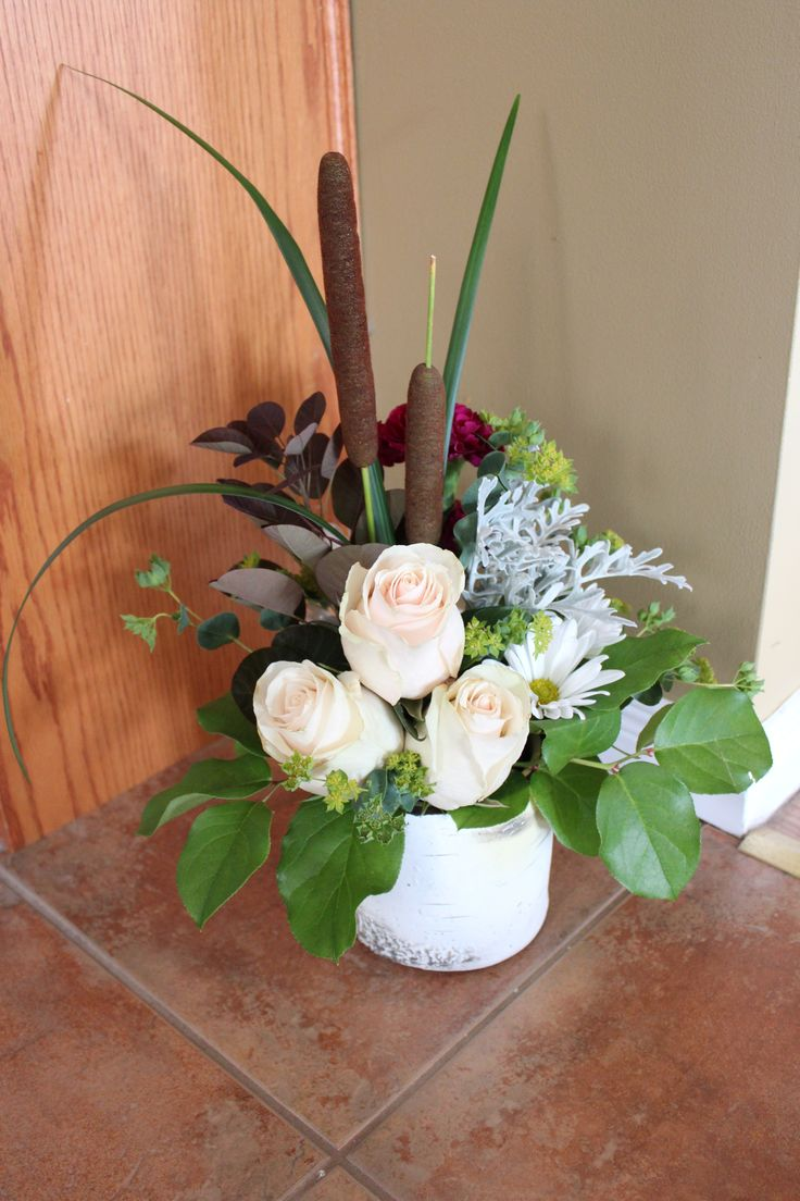 Nature inspired arrangement in a birch container.