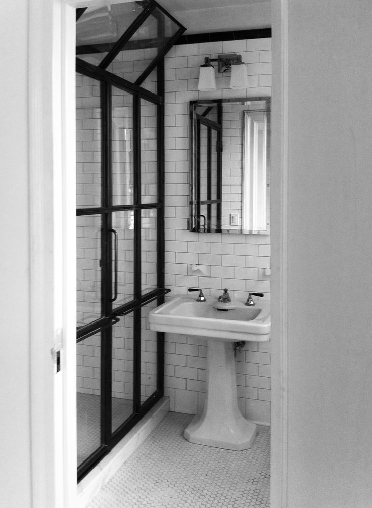 Custom blackened steel shower enclosure with operable factory window at top.