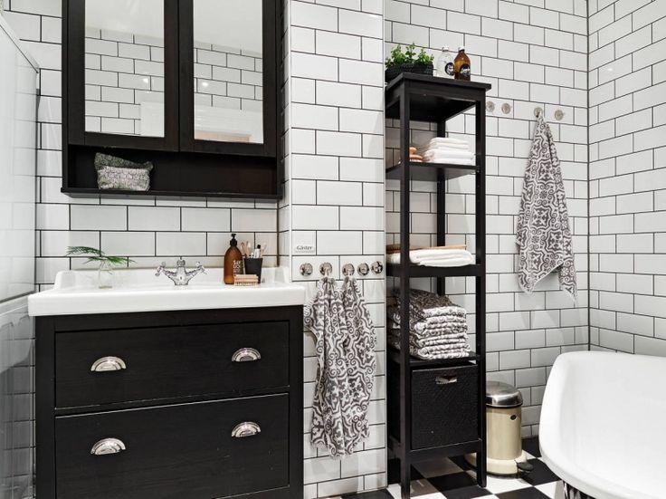 biała glazura cegiełka na ścianie w łazience, posadzka w szachownicę ,wolnostojąca czarna wanna i czarne etażerki z półkami w małej łazience - Lovingit.pl