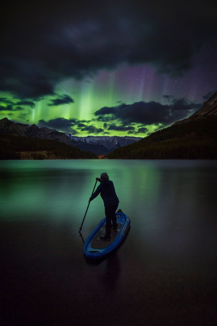 Aurora Glide - Sue Shih paddles her way towards the aurora on a magical night in the Canadian Rockies.