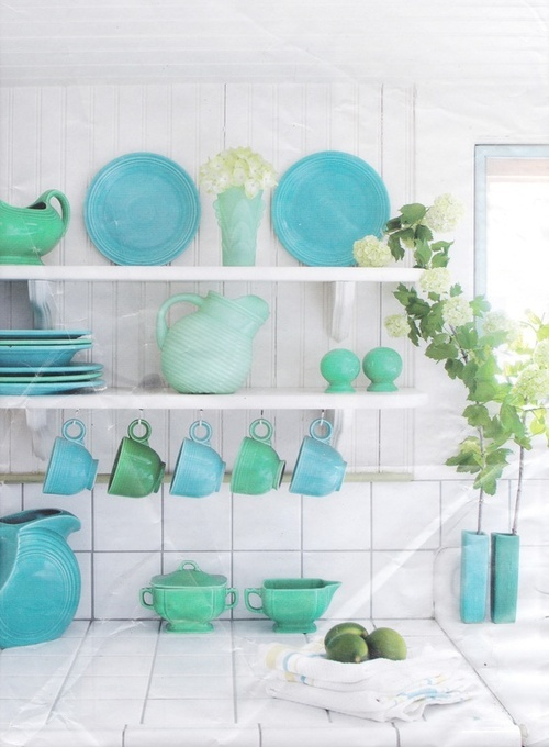 Colorful dishes popping off white open shelving, hanging mugs
