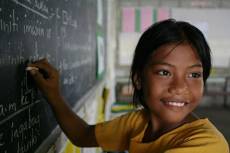 Rosemary, 9, writes on a blackboard in a primary school classroom in Tarawa, Kiribati. Kiribati is one of 14 Pacific Island Countries, which form a group of atolls dispersed over 30 million square kilometres of the Pacific Ocean. UNICEF is working with health ministries to improve birth registration practices and other child health initiates; deliver psychosocial support to children and families; and raise awareness of HIV/AIDS.  © UNICEF/Giacomo Pirozzi - http://www.unicef.org/photography