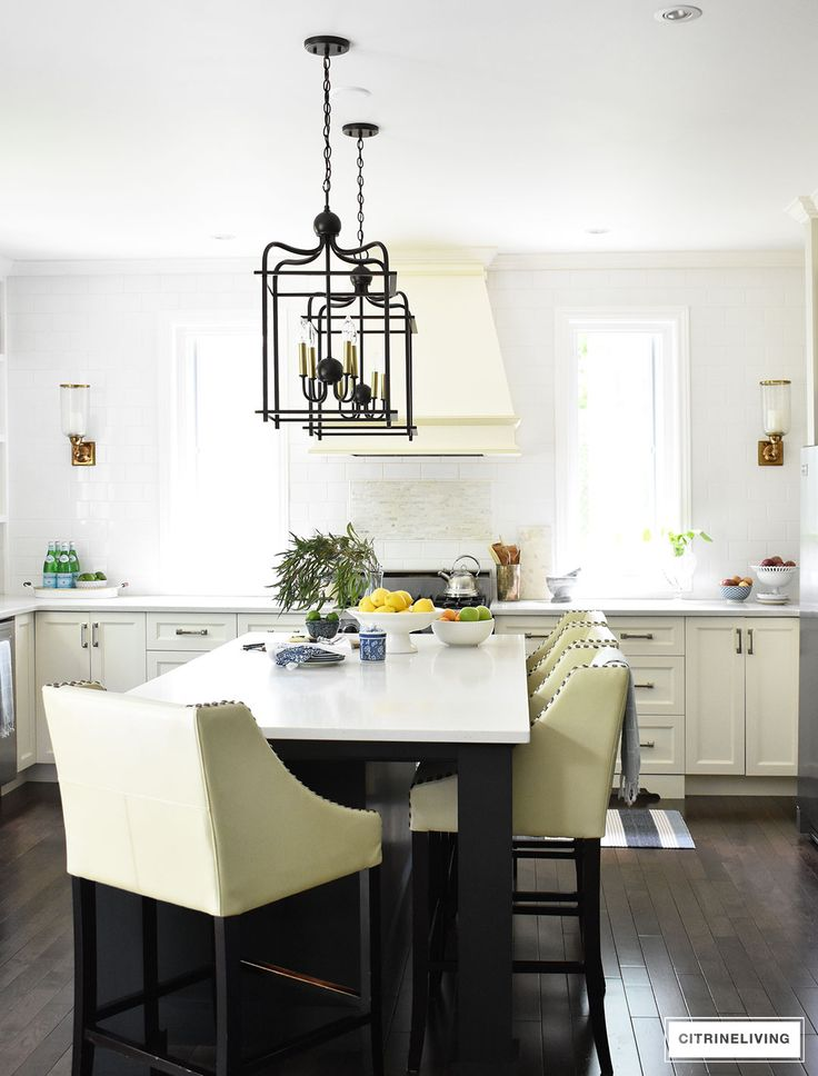 White kitchen with black island decorated for Summer with fresh cute greenery and bowls filled with bright, seasonal fresh fruit for a vibrant punch of seasonal color. Blue and white dishes and bowls are a classic touch. Lantern style pendant lighting over the island makes a bold statement.