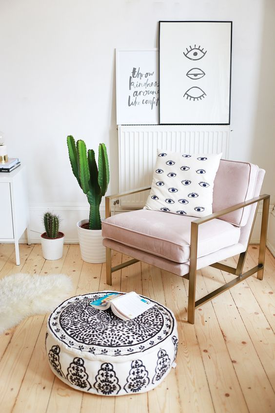 Feminine corner in the living room with cactuses and a pink armchair.