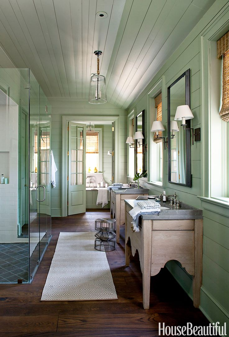 Designed to feel like an enclosed porch, this vintage-feeling bathroom designed by Bill Ingram in Lake Martin, Alabama, features lantern-style light fixtures, hidden medicine cabinets, and freestanding, antique oak washstands.   - HouseBeautiful.com