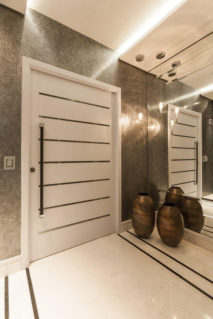 Immagine ingresso casa con porta blindata stile minimal moderno, abbinamento laminato bianco opaco e acciaio inox