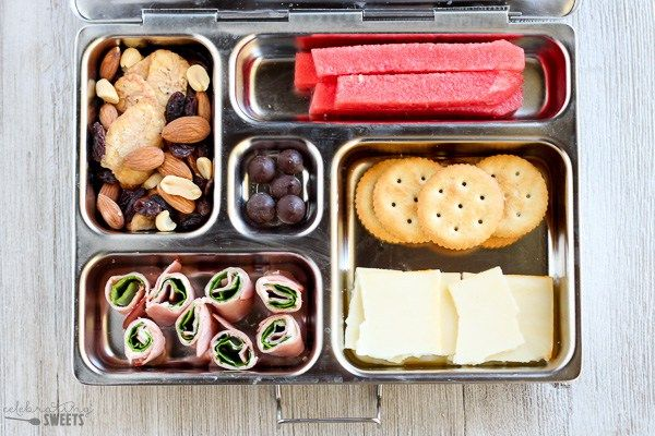 Trail mix, watermelon, crackers and cheese, ham and spinach roll ups, dark chocolate chips.