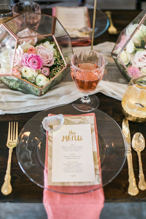 """""""We went for a glammed-up natural look,"""" says photographer Lori Blythe. """"Gilded geode slices graced marbled menus set atop crystal-clear plates on a farmhouse table accented with a gauzy runner and geometric terrariums brimming with soft flowers."""""""