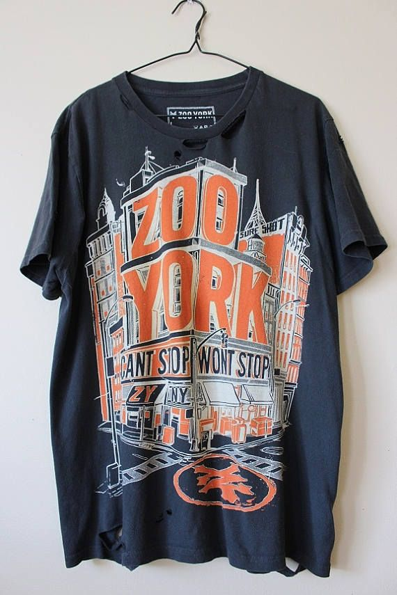 This shirt is a one of a kind, each shredded shirt is different.  This one is a cool dark navy blue Zoo York graphic tee , all cotton.  This shirt has distressing strategically placed all over the shirt including the collar, sleeves, front, back and the bottom hem.  Heres your info on it -  - Size Large, check measurements  - Across chest flat, pit to pit - 23 (46 around)  - Shoulder seam down - 28  If you need more info or have any questions, just yell, were around to help you out.  If…