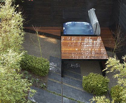 modern hot tub ipe wood cover that doubles as a tub deck and slides along rails across the yard