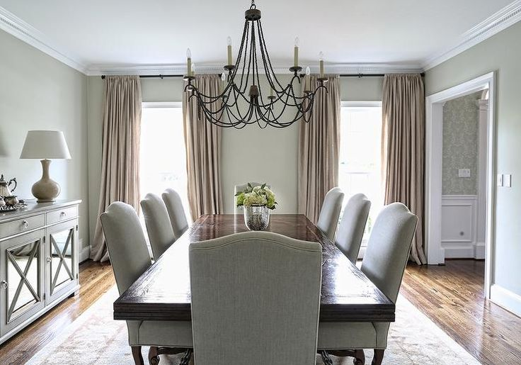 Elegant dining room features a stained dining table lined with gray linen nailhead camelback dining chairs illuminated by a black beaded chandelier placed in front of a gray sideboard cabinet fitted with mirrored doors.