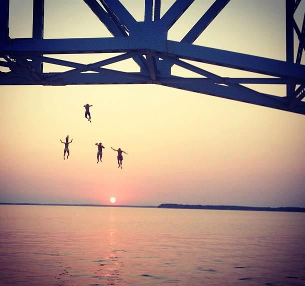 Summer adventure, beautiful sunset bridge jumping with friends.