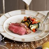 Barbecued leg of lamb with herb butter & zucchini, tomato & olive salad