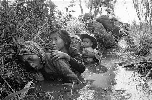 Niños y mujeres se protegen del fuego cruzado con el Vietcong agazapándose en una zanja (1966). (Horst Faas/AP)
