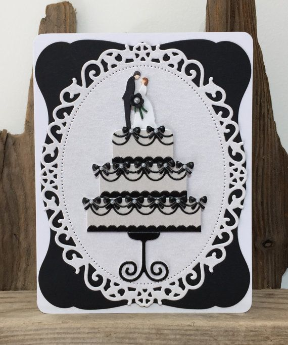 This handmade and unique Wedding card is made using black colour cardstock and complimentary pale ivory pearlescent paperstock.  A curved black frame sits on top of a white card base. On top sits a large Memory Box Stitched Oval Layer die cut from pearlescent ivory cardstock.  The centrepiece of this wedding cake card is a three tier cake cut using the Impression Obsession Wedding Cake die. The cake is cut from pearlised ivory cardstock and the icing and stand are cut from black cardstock…