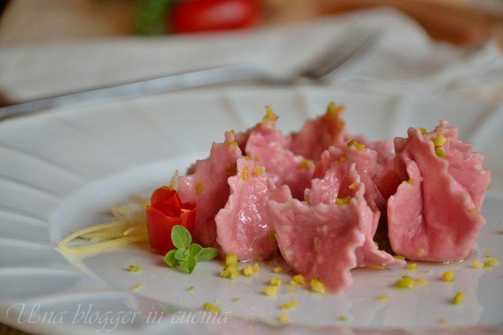 Fagottini rosa al salmone, zenzero e pistacchi, pasta fresca all'uovo con barbabietola, un ripieno di salmone, ricotta e zenzero e granella di pistacchi.