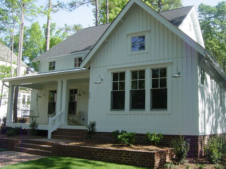 Just love this new farmhouse style home with batten board siding and brick foundation with planter boxes
