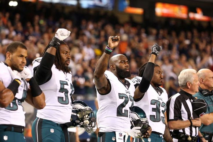 Philadelphia Eagles players Steven Means, Malcolm Jenkins and Ron Brooks raise their fists in the air during the national anthem for a game against the Chicago Bears on Monday, Sept. 19, 2016 at Soldier Field in Chicago.