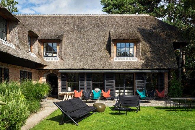 Un piacevole déhors nel verde: gli ospiti di Bea Mombaers a Knokke, in Belgio, possono godersi l'atmosfera rilassata seduti sulle tripoline colorare e sui divani neri da outdoor. La casa è una tipica abitazione in stile fiammingo, con tetto in paglia e struttura in mattoni.