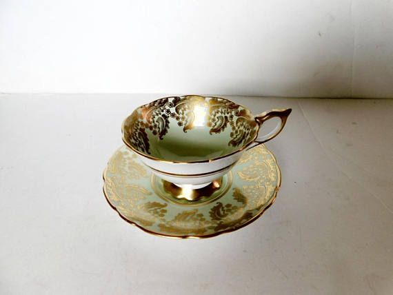 "Cup and saucer in pattern 8410G, a gold paisley like pattern on a pale green background, gold accenting  The cup is 2 7/16"" (6.2 cm) high x 4 1/8"" (10.5 cm) at the brim and the saucer is 5 13/16"" (14.8 cm) in diameter  Made of bone china from England by Royal Stafford  This set is in very good condition    These items have no nicks, chips, cracks, or signs of repair 