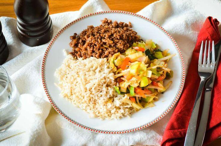 Recept voor sweet 'n sour wokschotel voor 4 personen. Met zout, olijfolie, peper, rijst, rundergehakt, Chinese roerbakgroente, woksaus zoet-zuur, ui en knoflook