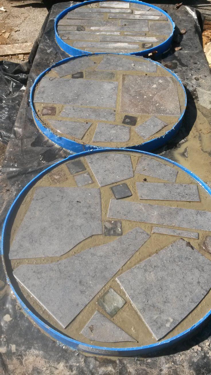 Concrete stepping stones.  Barrel rings, sakrete and tile scraps...