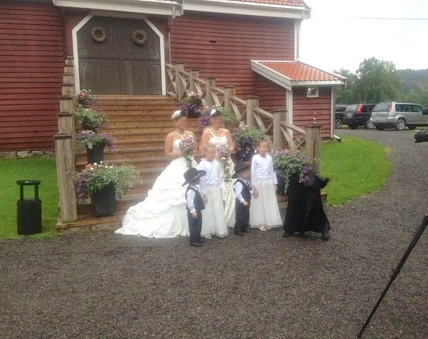 """This photo was taken at a wedding by a friend of a colleague. The wedding party was held at an old farm in Norway, famous for being the former home of M. Munthe (a children's book author). There was no one present at the wedding wearing black, and the picture was taken by one of the guests. The professional photographer had no 'natural' explanation for the 'figure.' He hadn't seen any camera 'glitch' like it before, and they said no one else was standing where the figure is standing."