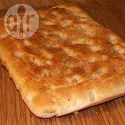 Фокаччо в хлебопечке. 1 стакан (230 мл) теплой воды 2 ст.л.оливкового масла 1/2 ч.л. соли 2 зубчика чеснока, измельчить 1 ст.л. мелко нарезанного свежего розмарина 3 стакана (400 г) хлебной муки 1 1/2 ч.л. (7 г) сухих дрожжей 2 ст.л.оливкового масла 1 1/2 ч.л. мелко нарезанного свежего розмарина (для украшения)