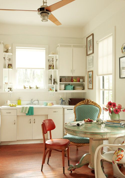 In this cottage kitchen, we again see touches of aqua paired with dusty rose. Simple cabinets are offset by a beautiful wood floor. Note the use of mismatched chairs around the painted kitchen table. I rather like it, do you?
