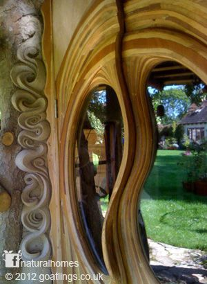 This stunningly beautiful door, surrounded by sculpted cob walls, is in a tiny cob home.
