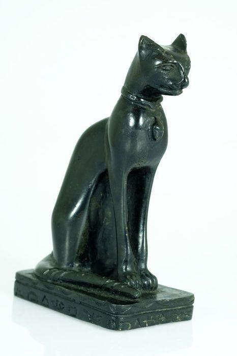 Kunstharsen beeld van Egyptische kat  Een fraai beeld van een Egyptische kat zittend in zijn bekende pose.Het beeld is gemaakt van kunsthars en komt vermoedelijk uit de 2e helft van de 20e eeuw.Details:Hoogte: 17 cm.Lengte: 11 cm.Breedte: 65 cm.Gewicht: 704 gram.Het decoratieve beeldje verkeert in goede conditie de foto's spreken voor zich.Het zal zorgvuldig worden verpakt en aangetekend worden verzonden (met track & trace).  EUR 3.00  Meer informatie