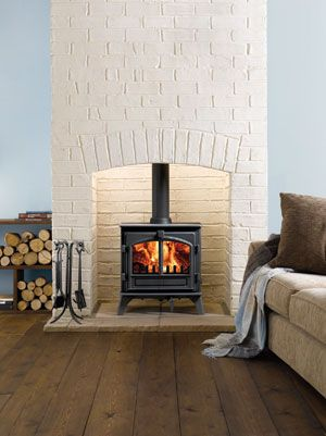 woodburning stove with white brick chimney breast