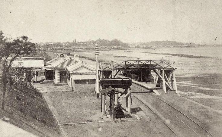 [過去写真]品川駅。明治五年(1872)に鉄道が開通した年の写真。東側はなんと遠浅の海。東京海洋大や天王洲などすべて海の底でした。この海は海苔の名産地で、収穫は浅草に運ばれ、浅草海苔と呼ばれました。棒状の煎餅に海苔を巻くと品川巻き。