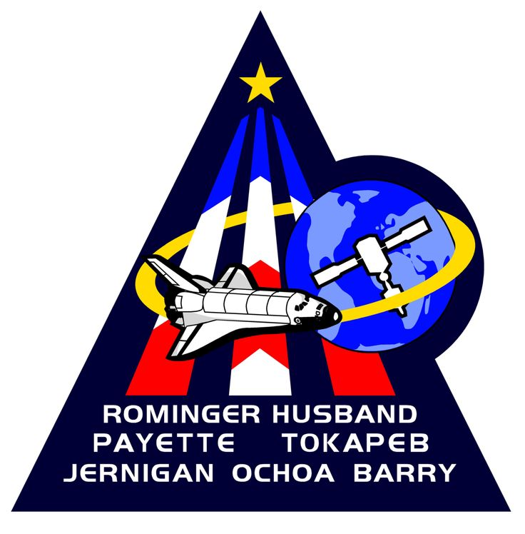 STS96-S-001 designed by the crew highlights the themes of the Station Program. The Shuttle is depicted preparing to carry out docking. The triangular shape represents building on the knowledge & experience of earlier missions, the 3 bars point toward future human endeavors in space. The star is symbolic of the 5 agencies in the development of ISS. The red, white & blue represents nationalities of the crew from the US, Canada, & Russia.