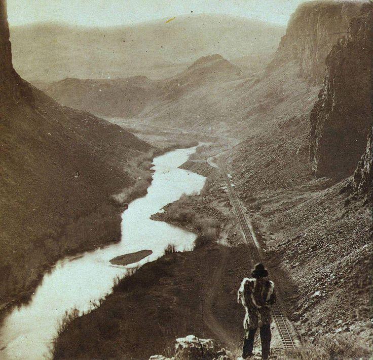 Коренной житель Америки смотрит вниз на только что построенный участок трансконтинентальной железной дороги, Невада, примерно 1868 год.