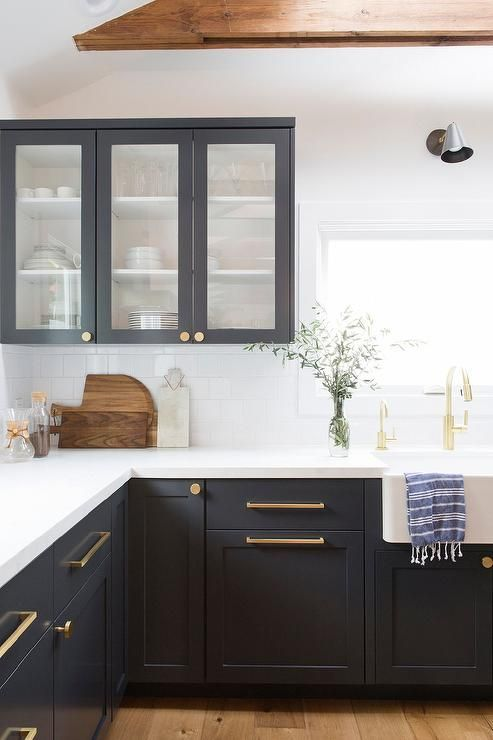 Chic two tone black and white kitchen is fitted with striking black shaker cabinets adorned with brushed brass pulls and a white quartz countertop.