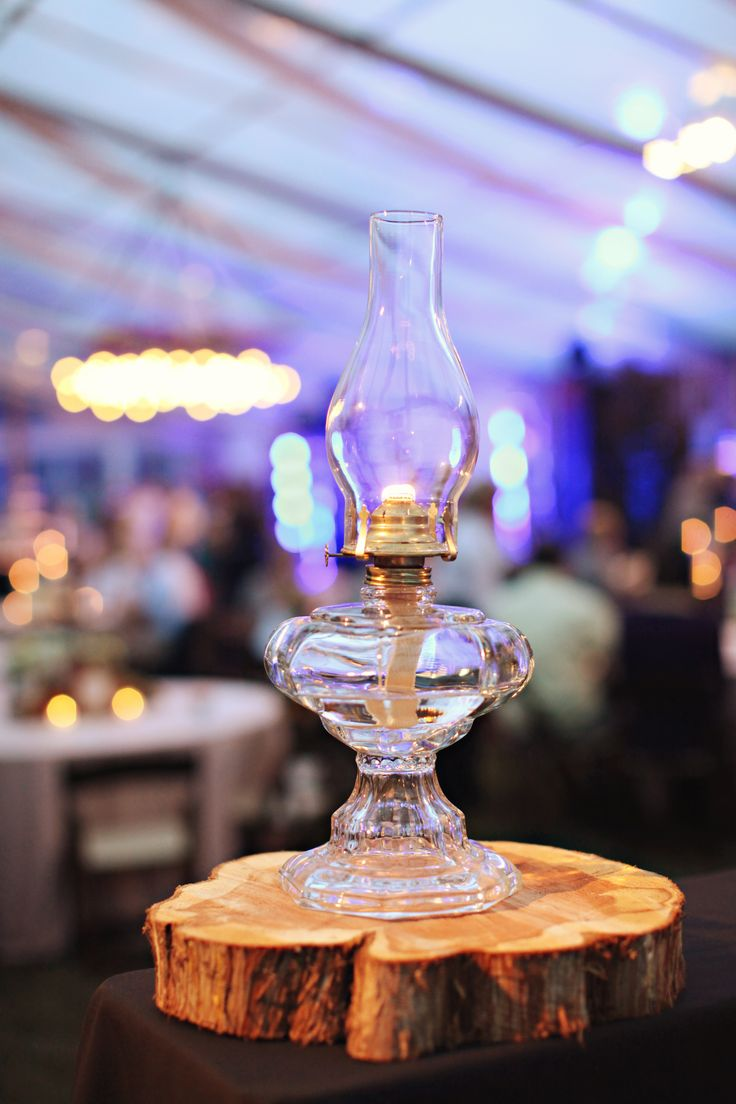Old fashioned oil lamps on slices of wood added decor to the lounge areas and bar tops.  Southern farm wedding decor.