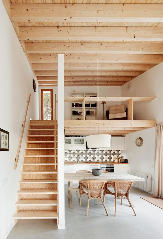 Open plan living space with exposed wood structure, wooden staircase and  mezzanine floor. Love