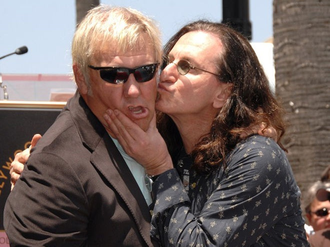 Geddy Lee kissing Alex Lifeson, possibly after singing an acoustic version of a song together--I've seen him do that. Old friends: great musicians.