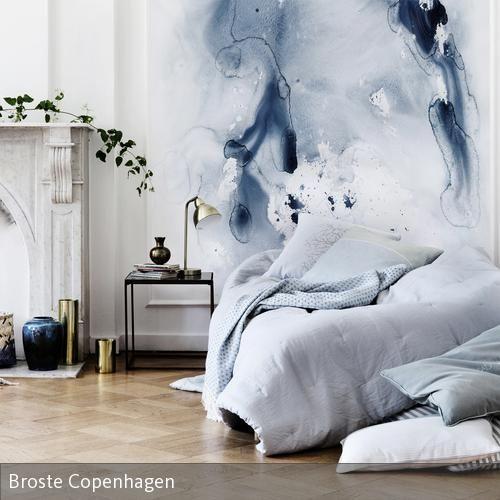 Blau und Grau dominieren den Look dieses eleganten Schlafzimmers. Ein abstraktes Wandgemälde dient als Blickfang am Kopfende des schlichten Bettes.  …