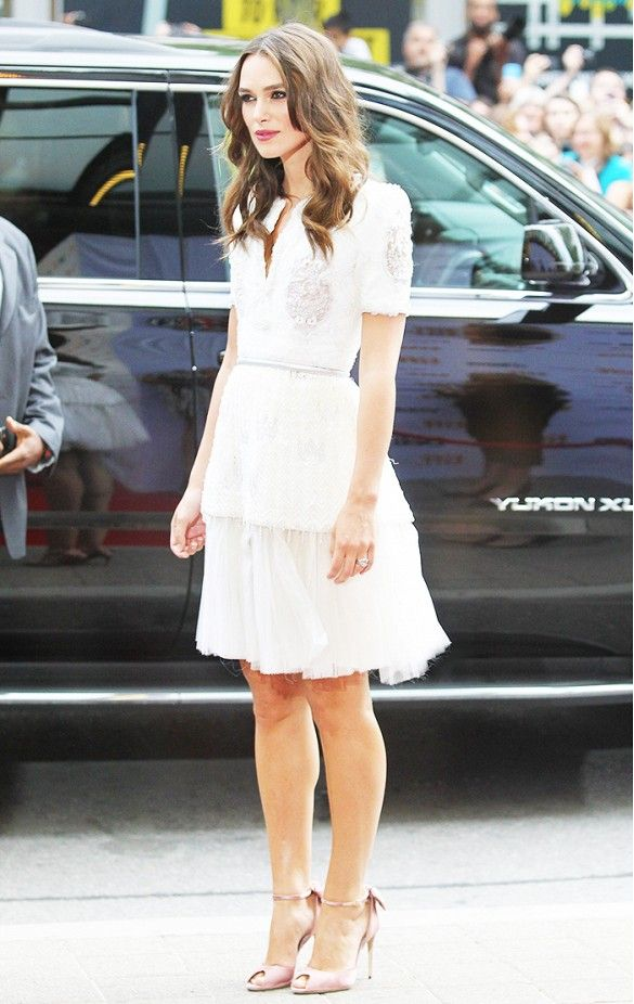 Keira Knightley wears a white lace belted dress with pink satin pumps