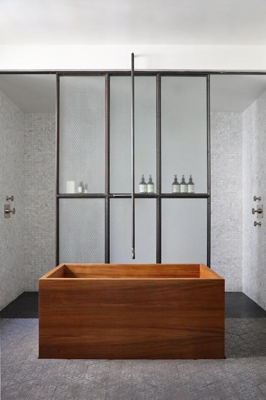 IL BAGNO Scultorea la vasca da bagno in legno di quercia al centro del locale bagno, con un originale punto acqua che scende dall'alto. Alle sue spalle un ampio vano doccia con doppio accesso, schermato da una vetrata industriale.