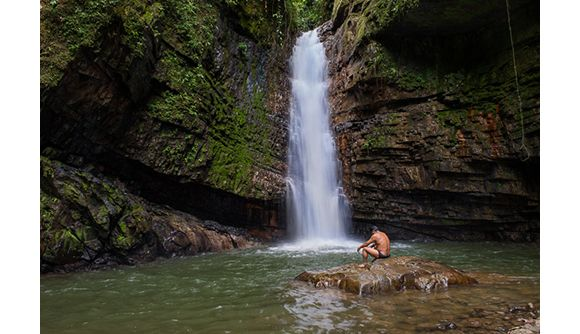 Shuar leader Patricio Tiwiram sits below a waterfall along the Rio Kupiamias. This is a sacred spot for the Shuar and one threatened by near...