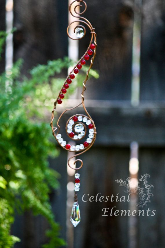Handmade Suncatcher the frame is copper, it's elongated, clear and red crystals wrap around wire, large crystal is suspended at bottom