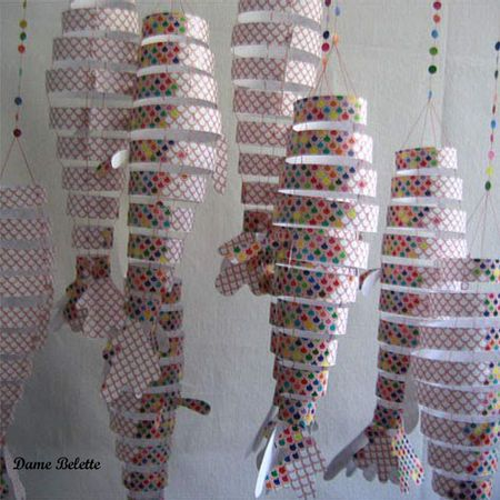 "10 rings of varying size; 3-4 tail fins; 2 little fins; held together via string stuck to the inside of each ring (4 strings used); each string should be about 1 meter long; use white pre-cut 1.5"" card-stock strips; let kids decorate then put together"