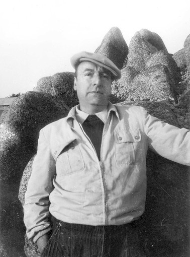 """neruda, in an undated photo, pauses on the beach in front of his house in isla negra. neruda gave the minuscule town the name """"Black Island,"""" inspired by the many volcanic-like rocks that speckle its beaches."""